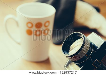 Old super 8 film camera with cup of coffee and accesories on background