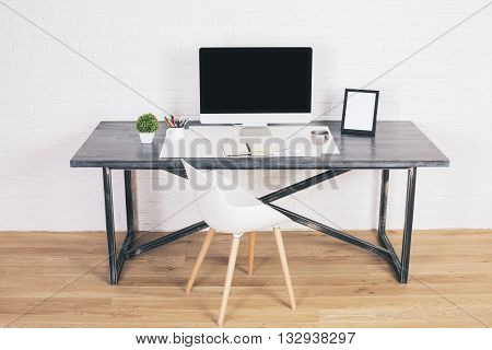 Designer desk with blank computer screen picture frame and modern white chair next to it on wooden floor and brick background. Mock up