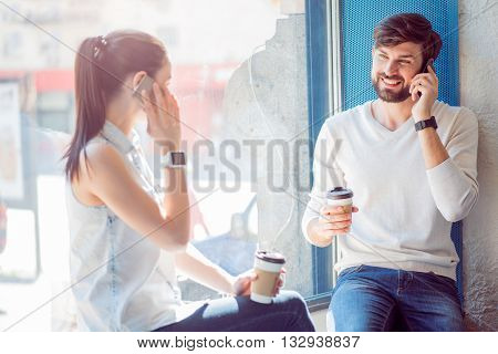 Modern communication. Smiling and merry modern young woman and man sitting in a cafe on a window sill, drinking coffee and talking on their cell phones
