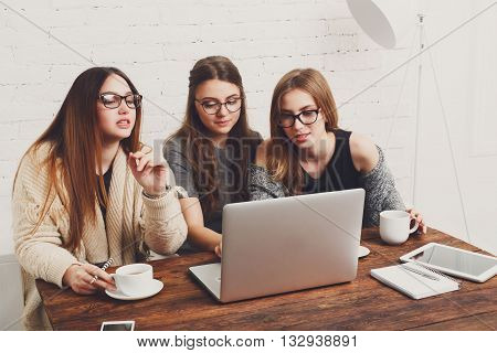 Three girls work and coffee with laptop. Young girls friends happy with computer. Discussion, startup, friendly conversation. Women friendship, modern life, gossip and internet dating concept.