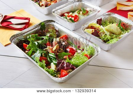 Healthy food delivery. Fitness food. Weight loss nutrition diet. Eat right concept, healthy food, clean food take away in aluminium boxes, vegetable salads and meat at white wooden table closeup