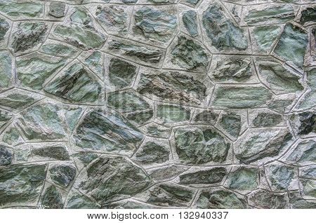 green stone wall house facade background detail