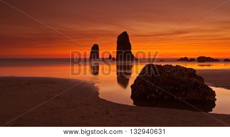 Quiet summer sunset at Cannon Beach, Oregon, USA - wet sand, sky reflections in the water.