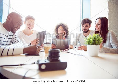 Informal workshop. Cheerful and smiling young group of people sitting together and discussing their business plan while using various modern devices