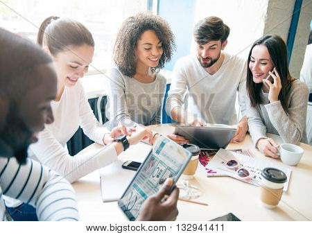 Informal business gathering. Positive and cheerful group of young professionals sitting together and talking about their business future while using various modern devices and drinking coffee