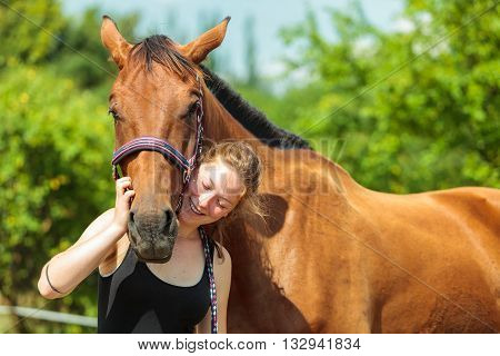 Young woman girl taking care of brown horse. Female with animal outdoor.