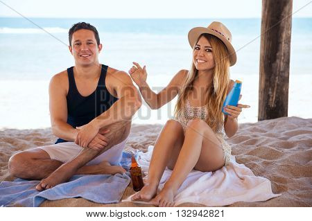 Newlyweds Putting Sunblock On At The Beach