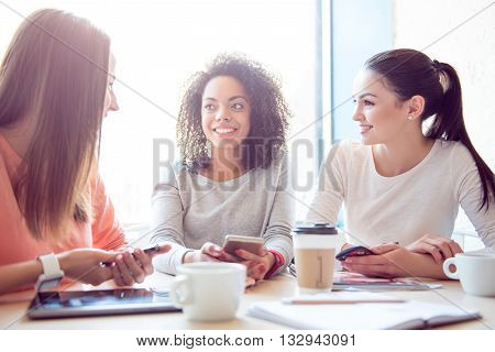 Gossiping together. Cheerful and delighted young women sitting and discussing different things while being in a cafe and using their cell phones