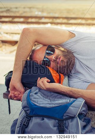 Closeup of handsome male backpacker tourist napping on a bench and baggage at the station