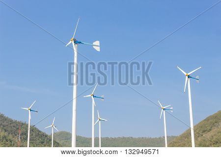 Wind Turbine for alternative energy on background Sky and Mountain.