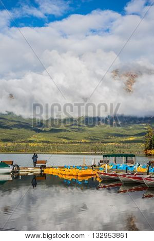 The wooden boat mooring with the moored boats. On the mooring there is elderly woman with camera. Cumulus clouds over the Pyramid mountain and Pyramid Lake