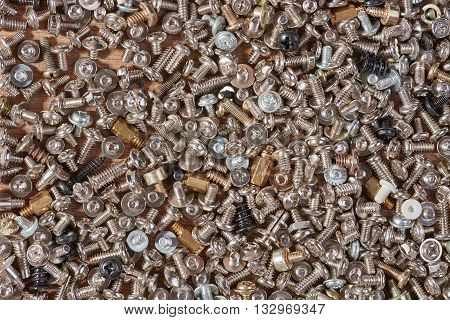 small fixing screws are scattered on a wooden board to use as a background