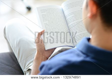 A Man Reading Book While Sitting On The Couch