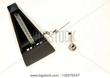 Metronome and mouthpiece of a trumpet isolated on a blank white background as copy space