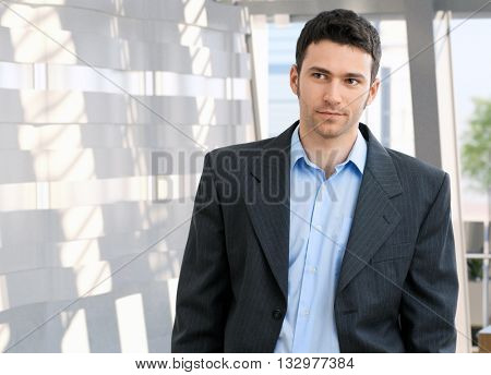 Portrait of young caucasian office worker. Suit no tie, copyspace.