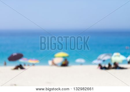 Blurred blue sea and white sand beach with parasol, beach chair and some people - holiday and vocation background concept