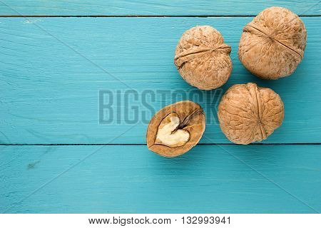The concept of healthy eating. Love for healthy food, nuts. The heart of walnut on a blue wooden background