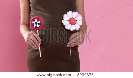 Pregnant woman holding candies near her belly. Conceptual image with candies representing a baby boy or a baby girl.