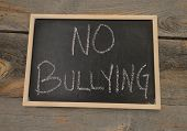 Anti-bully message or no bullying written in chalk on a chalkboard on a rustic background poster