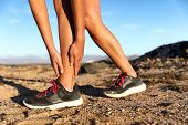 Runner woman with hurt ankles in pain during marathon. Athlete woman running outside with body injury. Sprained ankle on trail run in summer outdoors nature. Fitness leg accident on cardio workout. poster