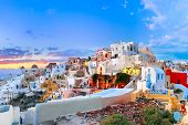 Picturesque panorama, Old Town of Oia or Ia on the island Santorini, white houses, windmills and church with blue domes at sunset, Greece poster