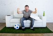crazy football fan cheering happy watching television soccer match celebrating scoring goal excited and euphoric sitting on sofa couch with ball and grass carpet emulating stadium pitch poster