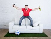 crazy football fan in red team jersey cheering happy watching television soccer match celebrating scoring goal excited and euphoric in sofa couch with ball on grass carpet emulating stadium pitch poster