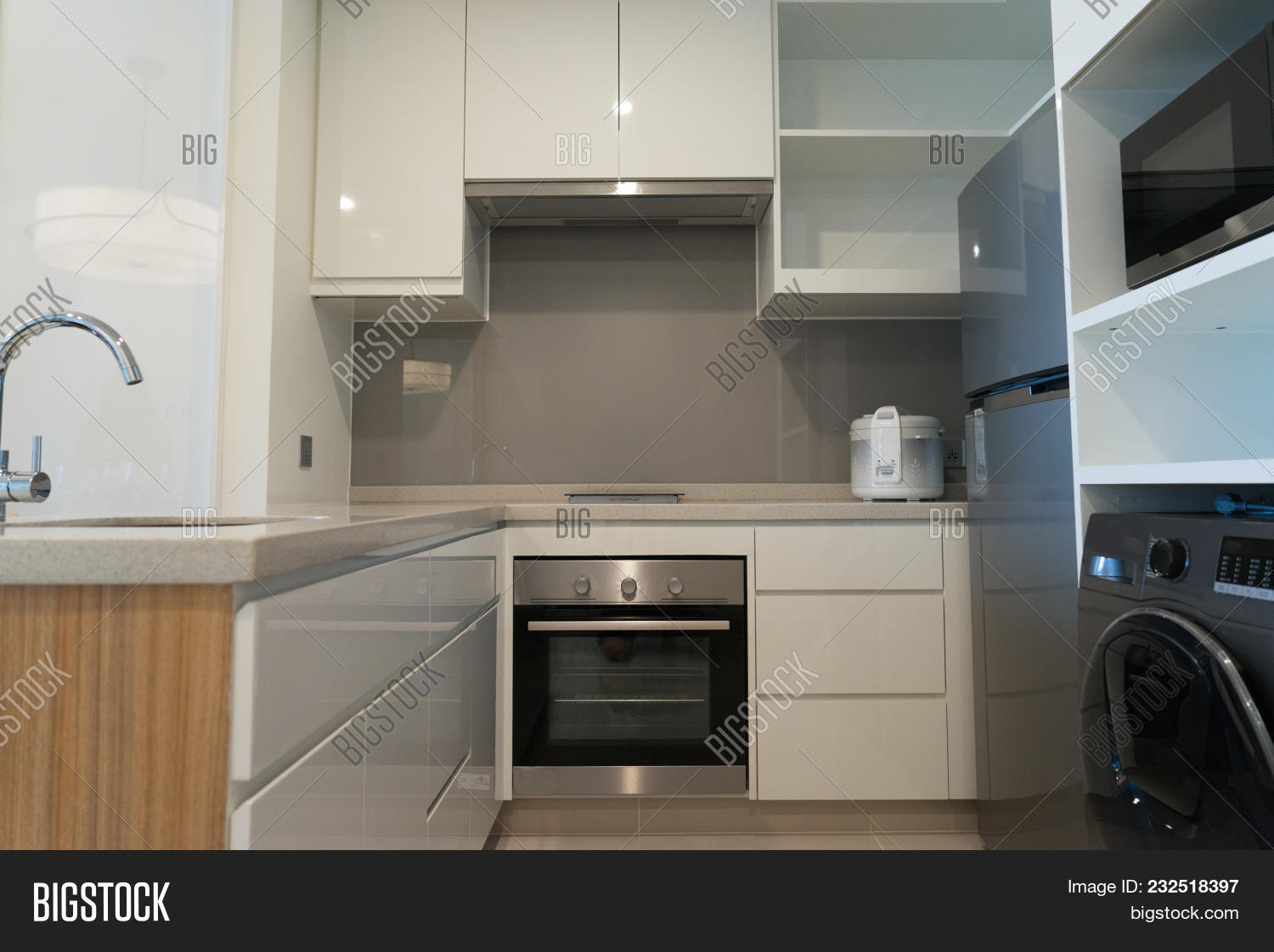 Small kitchen set equipped with appliances such like freezer washing machine microwave electric oven and stove cooking area concept