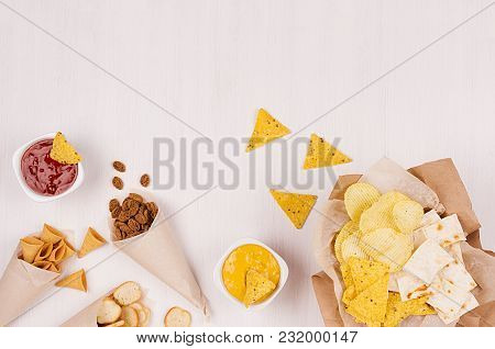 Golden Different Snacks On Craft Paper Cone, Triangles Nachos, Sauce In Bowl On Soft White Wood Back
