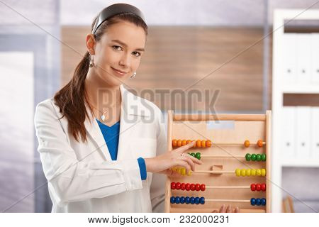 Young female teacher teaching mathematics in elementary school classroom, looking at camera, smiling.