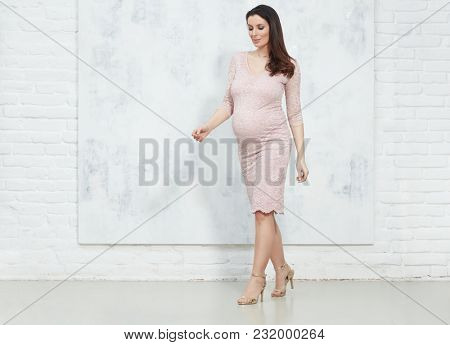 Fashion portrait of happy pregnant woman in elegant dress against white wall with copyspace.