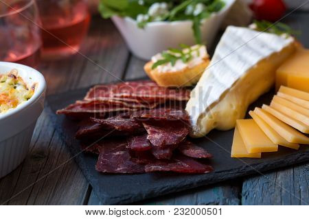 Board With Basturma, Salami, Camembert, Cheese, And Other Delicacies