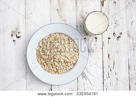 Oatmeal, Rolled Oats On A Plate With Glass Of Milk On White Wooden Table. Porridge Oats, Used In Gra
