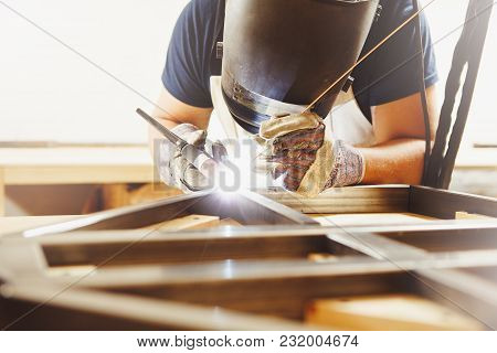 Male In Face Mask, Protective Gloves Welds With Argon-arc Welding. Welder Makes Weld Seam On Metal F