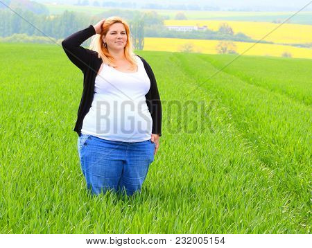 Obese farmer woman inspecting her plantations. Happy life on Czech countryside. Sustainable development in European Union.