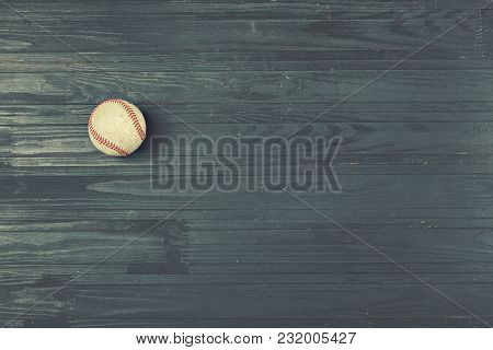 Old Baseball Ball On A Wooden Black Background With Copy Space