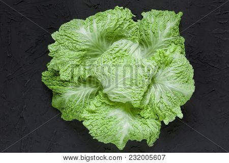 Green Batavia Lettuce Salad Head Top View On A Black Stone Table