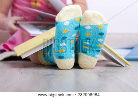 Small Child In Funny Socks In Polka Dots, Reading Books. Close-up