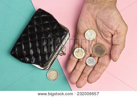 An Elderly Person Holds The Coins Over The Old Empty Wallet. The Concept Of Poverty In Retirement.bl