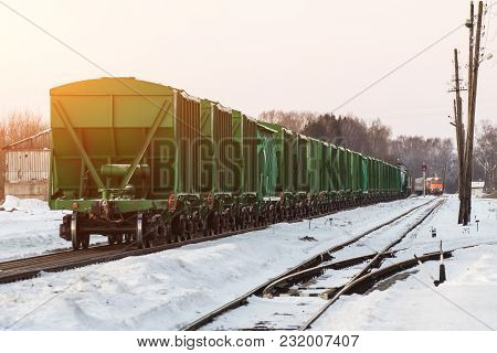 A Freight Train With A Small Train Of Hopper Cars, At A Small Station In Winter. A Different Locomot