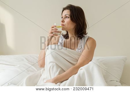 The First Morning Drink Of An Adult Mature Woman Is Antioxidant - Water With A Lemon, Sitting In Bed