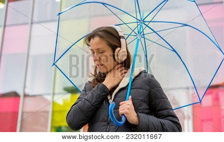 symptom sore throat, woman with fever and discomfort from the cold and winter flu, girl in the street with a transparent umbrella with signs of illness