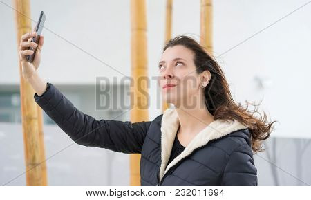 taking a selfie, Brown-haired woman in video conference with the mobile. talking on the street with your partner through the use of new technologies