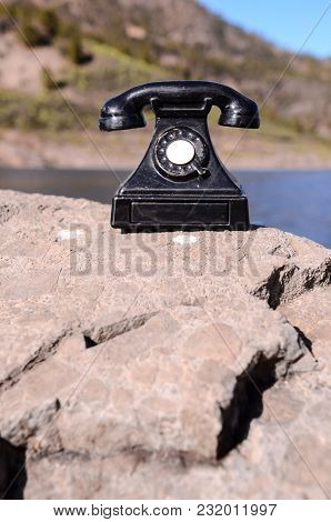 International Communications Vintage Telephone Toy On The Volcanic Rocks