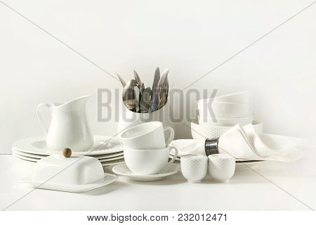 White Tableware For Serving. Crockery,dish, Utensils And Other Different White Stuff On White Table-
