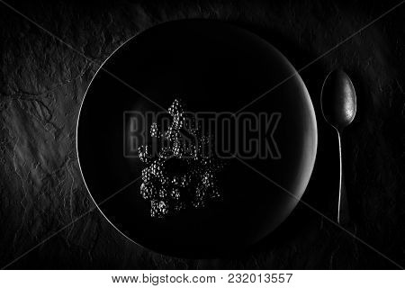 Blackberries on a black plate and dark slate background with spoon