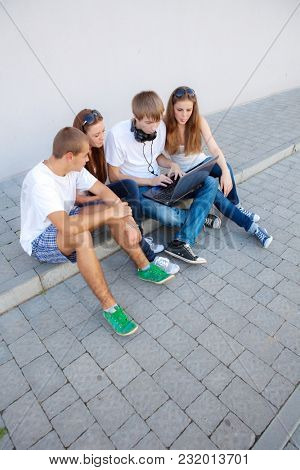 group of young people with laptop on the street