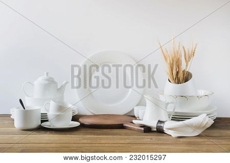 White Kitchen Utensils, Dishware And Other Different White Stuff For Serving On White Wooden Board.