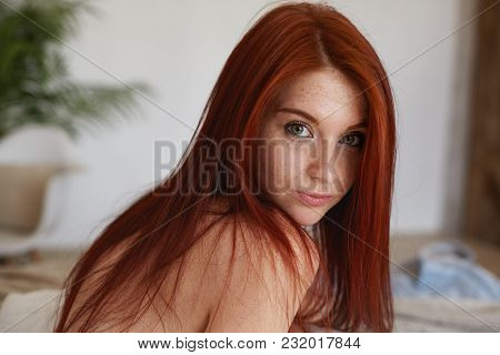 Indoor Portrait Of Amazing Young Freckled Red Haired Female Of Natural Beauty Posing At Home Wearing