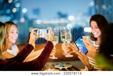 Girl friends having a dinner together at a rooftop bar taking a photo of the toast social media concept